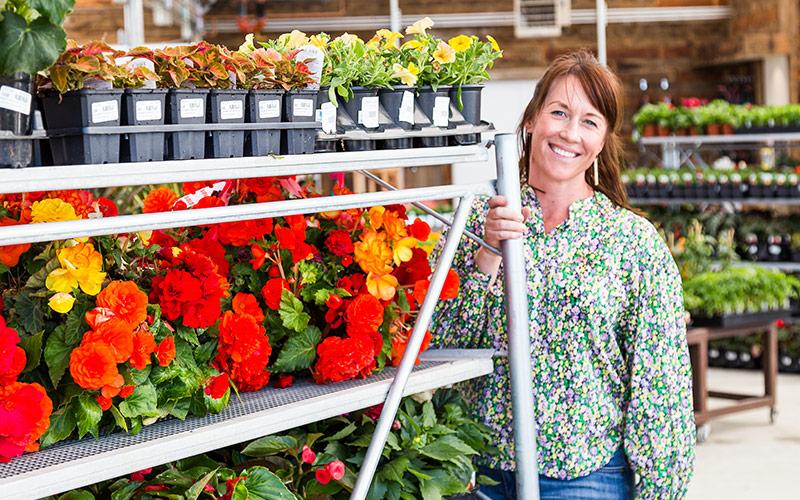 Sara Cimbalik, Garden Center Vice President showcasing colorful annuals on a cart.